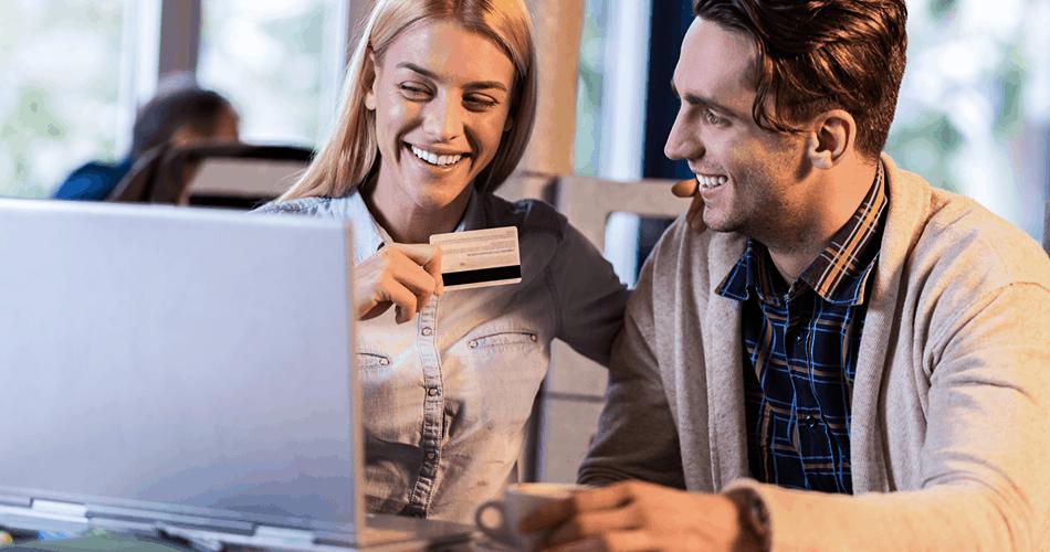 Uśmiechnięta para płacąca w sklepie internetowym kartą kredytową