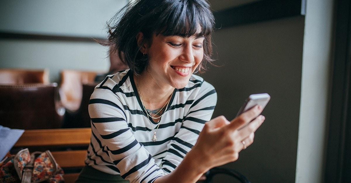 Uśmiechnięta osoba korzystająca ze smartfona