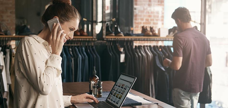 Sprzedawca korzysta z komputera i telefonu w sklepie odzieżowym